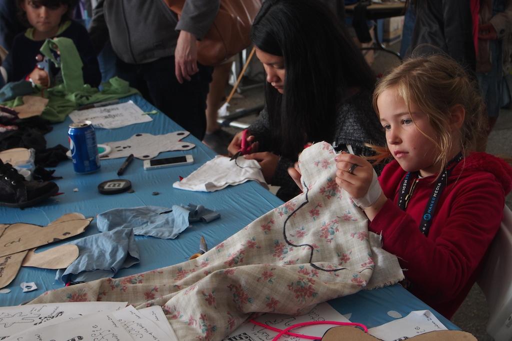 小女孩剪裁自己的布玩偶。